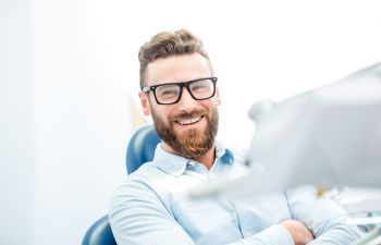 Satisfied man with a perfect smile sitting in a dental chair.