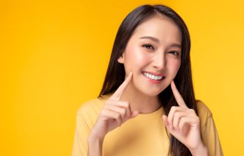 Young happy Asian woman pointing at her perfect teeth
