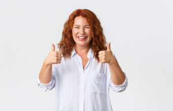 Happy middle-aged woman with a perfect smile showing her thumbs up.