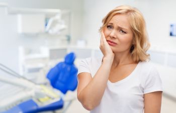 Upset woman with dental problem at dentist's office.